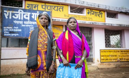 Pavitri Manjhi, a Human Rights Defender from Chattisgarh, India stands with another women in front of a shop.