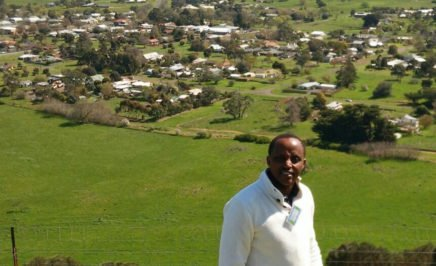 Man with dark skin in business attire with green, rural farmlands behind him.