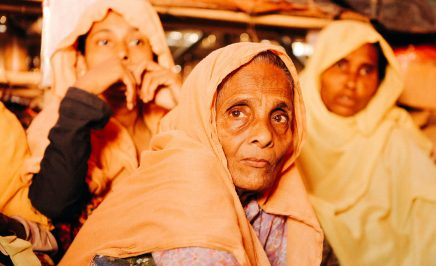 Three Rohingya refugee women staring into the camera. An older woman sits in front of two younger women.