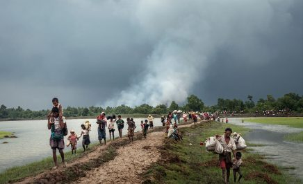 Rohingya refugees stream into Bangladesh after crossing the Naf River, which separates Myanmar and Bangladesh, in September 2017. In the background, smoke rises from villages being burned in northern Rakhine State, Myanmar.