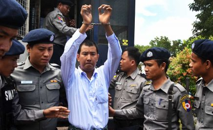 A man is walking with his hands cuffed above his head. He is flanked by six members of the Myanmar police force.
