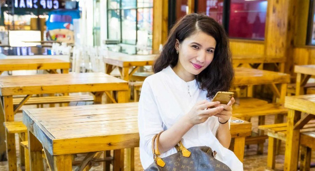 A woman (Uyghur student Guligeina) sits in a cafe full of wooden chairs and tables. She wears a white shirt, is smiling and holding her phone.