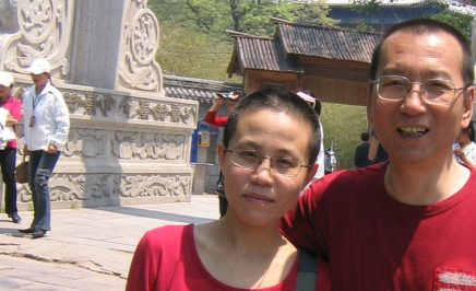 Chinese artist Liu Xia with her late husband and Nobel laureate Liu Xiaobo. Both are looking at the camera and wearing red tshirts. The man is smiling.