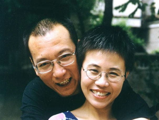Chinese artist Liu Xia with her late husband and Nobel laureate in 2001. Both are smiling and have their arms around each other.