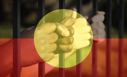Children's hands with Indigenous Flag overlay