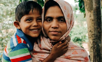 A Rohingya woman and her young son smile at the camera