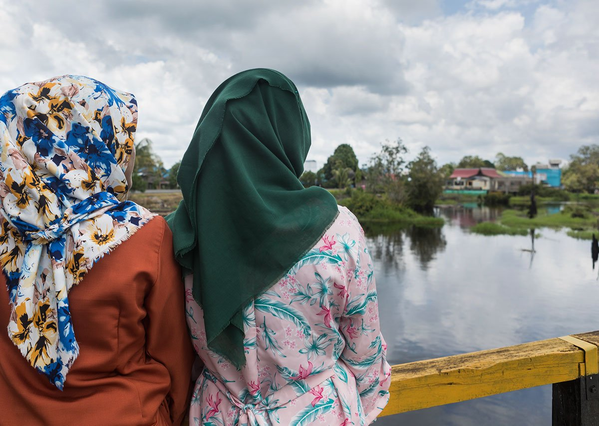 An image of three Indonesian women staring out over a river towards a village in the distance. The women have their backs to the camera and are wearing brightly coloured head scarves.