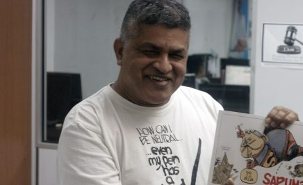 Zunar holding his book 'Sapuman, Man of Seel'. © Amnesty International