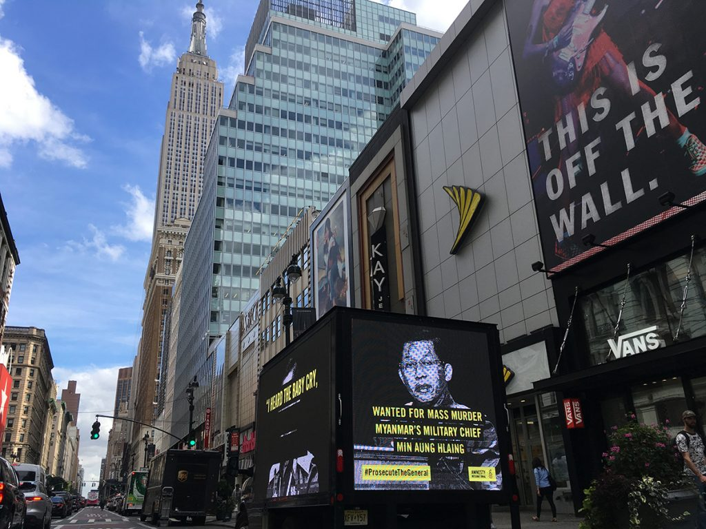 Wanted poster of Myanmar's top military general, Min Aung Hlaing, on a billboard in New York. Backdrop of iconic New York skyscrapers.