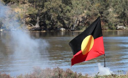 Aboriginal flag fluttering in the breeze with a river in the background