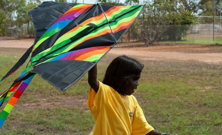 A young girl wearing a yellow t-shirt runs through a field flying a brightly coloured kite above her.