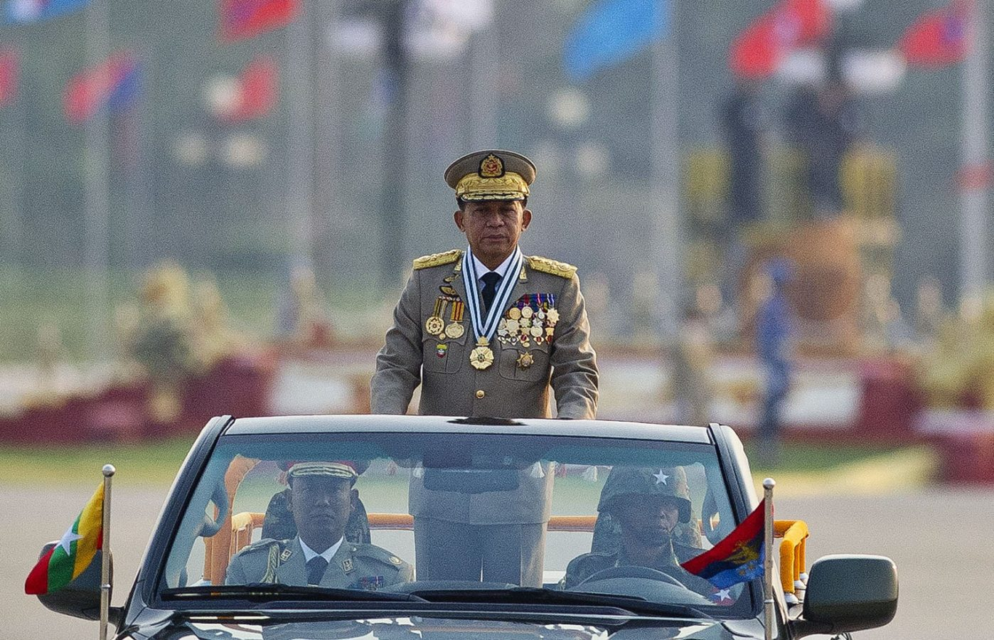 A man in a Myanmar military uniform stands up in an open-top car at a military parade. There are two other people in the car with him, also in military dress. Blurred in the background we can see a line of flags from different countries.