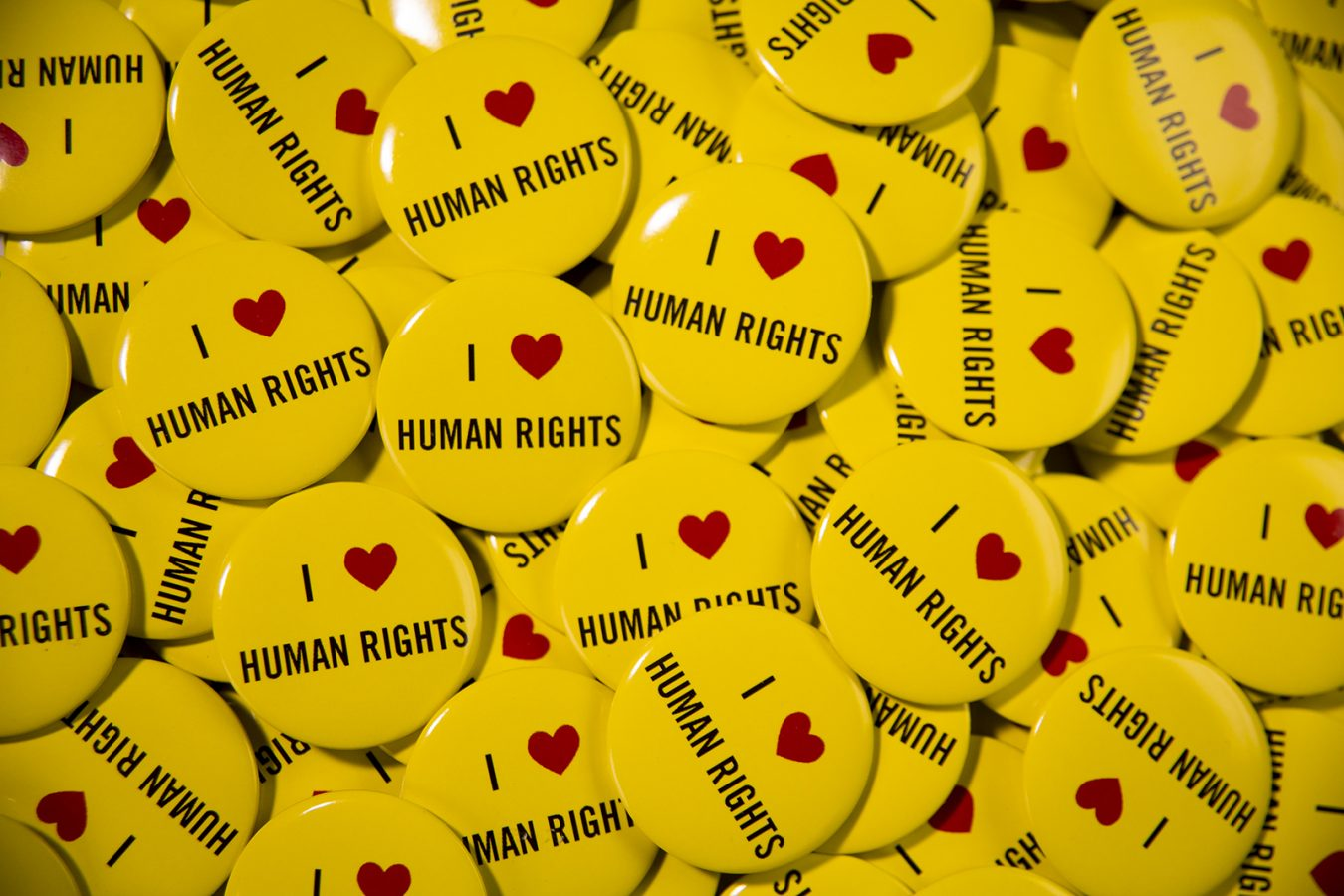 Hundreds of yellow badges with 'I heart human rights' printed on them.