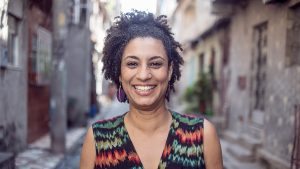 A woman wearing a brightly coloured dress smiles into the camera. A street stretches out behind her.