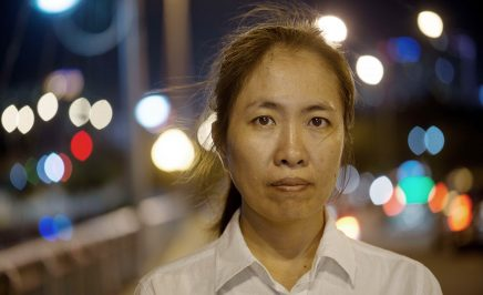 A Vietnamese women wearing a white shirt stares into the camera. It is nighttime and the lights of a city twinkle behind her.