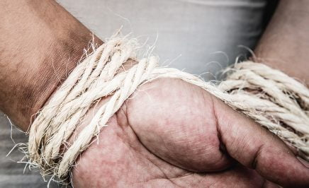 A photo of a man's hands bound behind his back with fraying twine or rope.