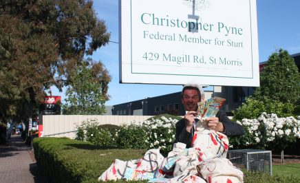 man sits in front of sign saying 'christopher pyne federal member for sturt' with a paper mask, holding bags of money