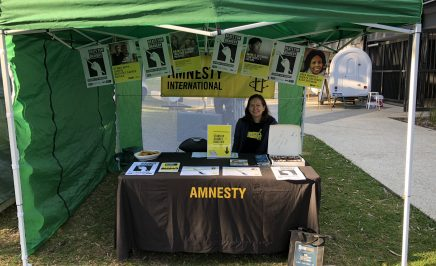 Volunteer sitting at Amnesty marquee stall covered in Amnesty promotional material