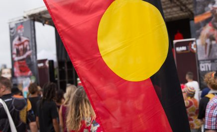 The Aboriginal Flag being flown at Yabun Festival 2018, in the distance is a stage and festival participants