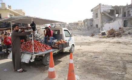 Farmers in Syria unloading vegetables from a flatbed truck.