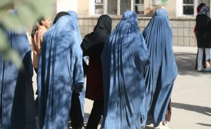 Afghan women dressed in blue with their backs to the camera on their way to vote.