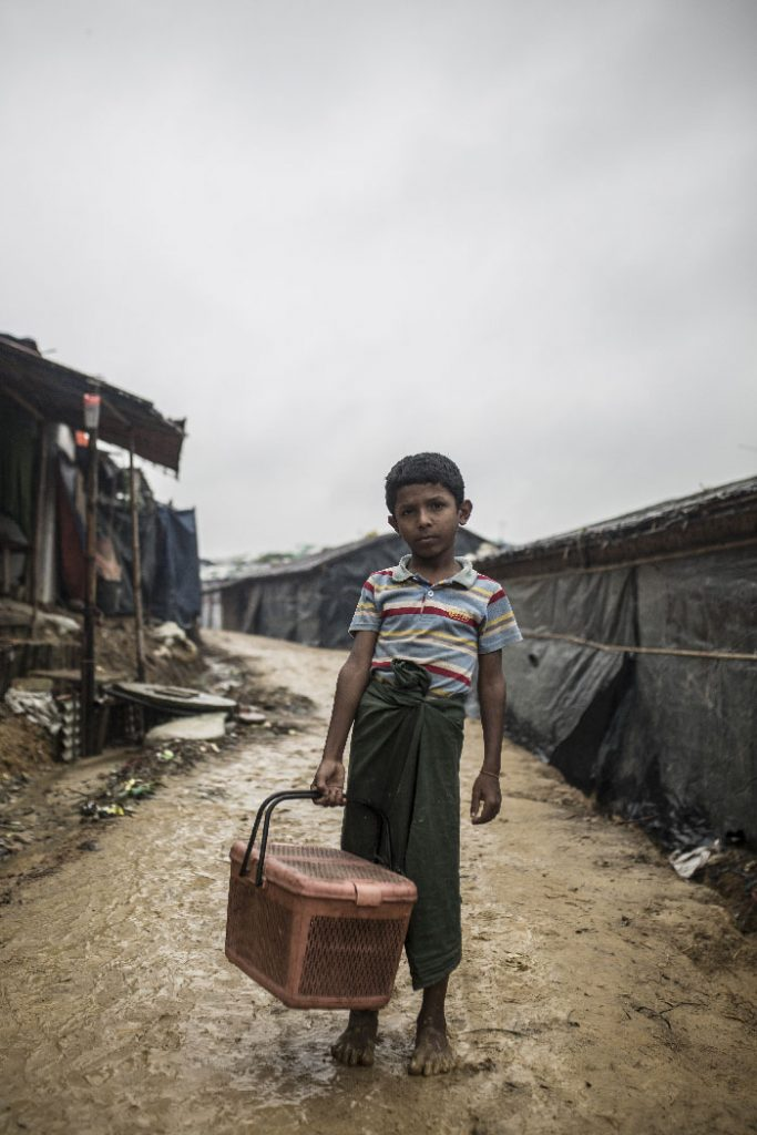 A young boy stands on a muddy path between makeshift refugee tents and looks into the camera. He is carrying a basket.