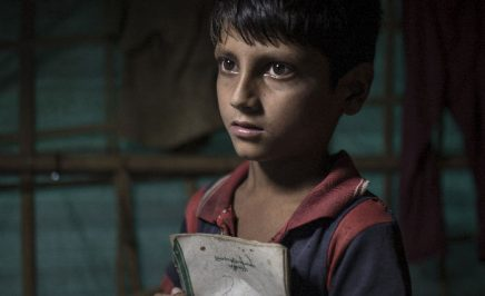 A young Rohingya boy holds a school book in a refugee camp in Bangladesh.