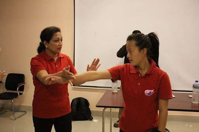 A women in a red t-shirt is teaching self-defence another woman in a red t-shirt.