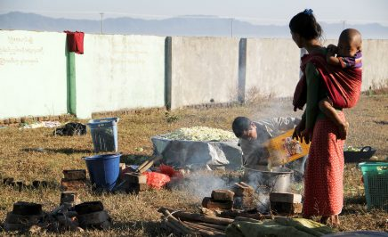 A woman with a child strapped to her back stands on grass watches as a man pours water for cooking rice into a large pan. In the background is a wall and living utensils are scattered around them on the grass.