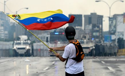 A Venezuelan opposition demonstrator waves a flag at the riot police in a clash during a protest against President Nicolas Maduro, in Caracas in 2017.
