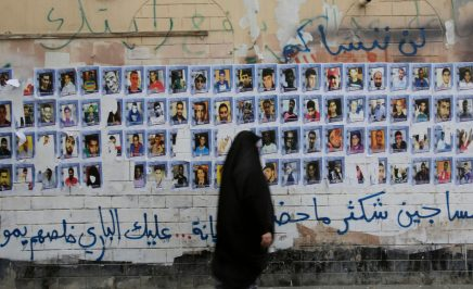 A woman wearing a black headscarf walks past photos of people pasted to an old building's wall, with crumbling plaster. Above and below is spray-painted Arabic words