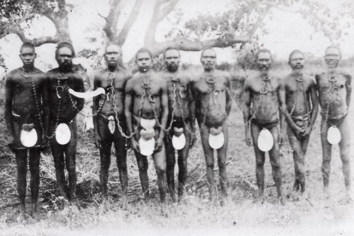 Black and white blurry image of Aboriginal people stand in a row, chained together by their necks, wearing riji (carved pearlshell) as they stand in the mangroves of Broome, c. 1910.