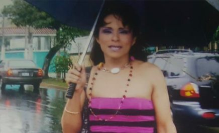 Alejandra, a transgender woman and activist from El Salvador stands in the street with an umbrella.
