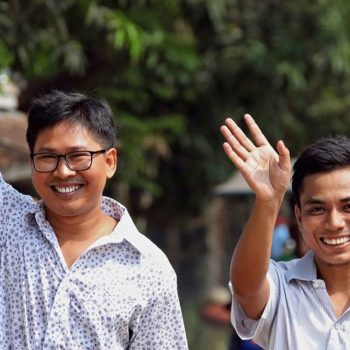 Wa Lone and Kyaw Soe Oo smile widely and wave. Wa Lone has his hand raised in the air in a thumbs up.