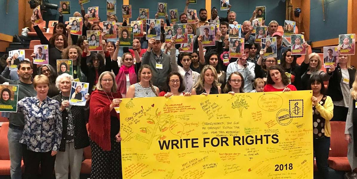 a big crowd of people hold up a yellow banner that says Write for Rights