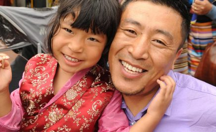 A man and a young girl smiling into the camera. Both are of Asian descent.