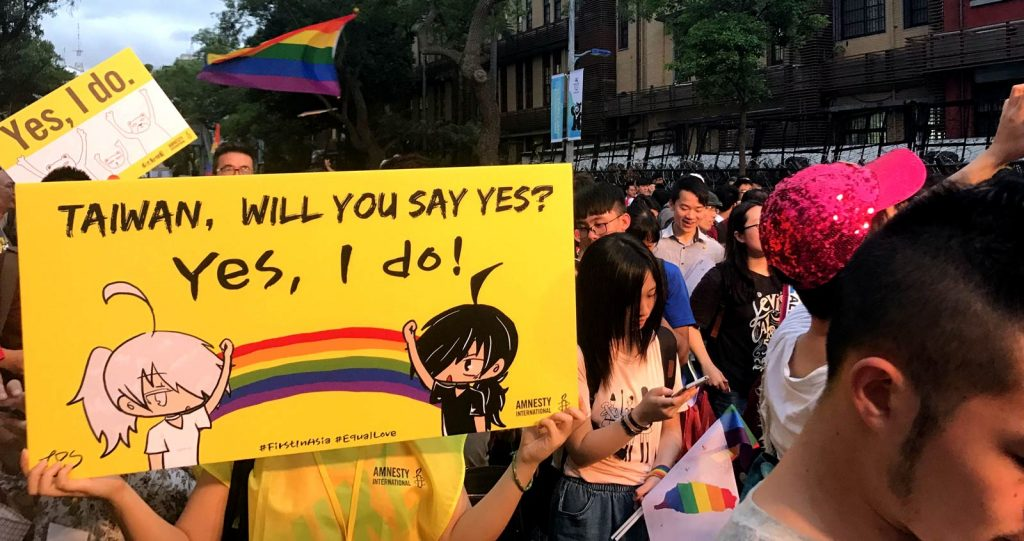 Crowd of people with rainbow flags. One person holding a yellow sign with a rainbow and words: Taiwan, will you say yes? Yes, I do!