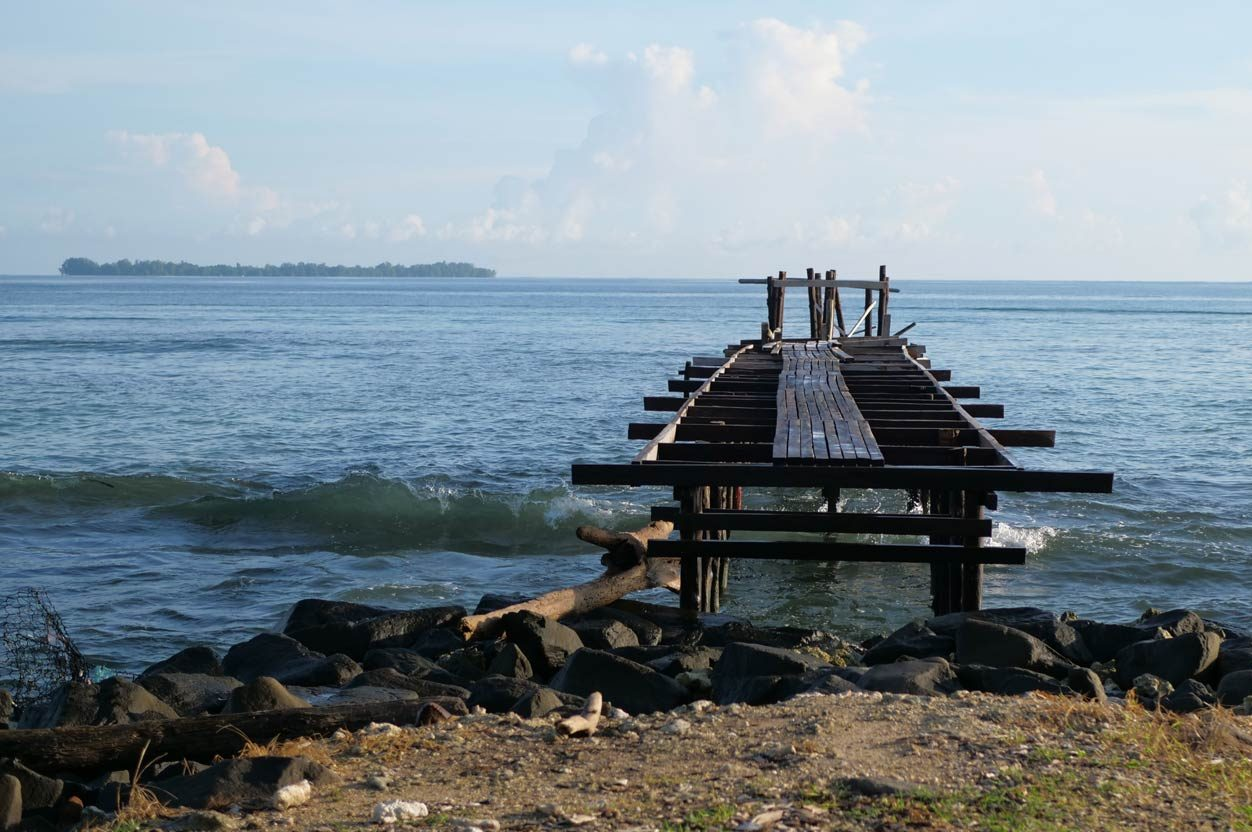 An old wooden jetty over a clear ocean water and with a sandy beach