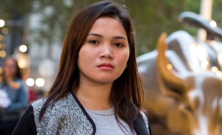 A young woman stares directly into the camera, a statue of a golden bull from Wall Street softly out of focus behind her.
