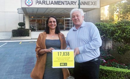 A man and a woman hold a yellox box with a sign on it reading: 17,838 people signed to get kids out of watch houses