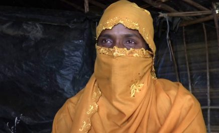 A woman wearing an orange headscarf. The walls of a makeshift shelter are behind her: black tarp and bamboo lattice work.