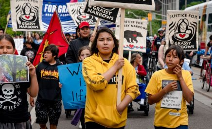 A group of young people holding placards on the street. Grassy Narrows demonstration,Toronto, Canada.