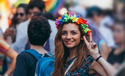A woman wears a rainbow flower crown and performs the peace sign.