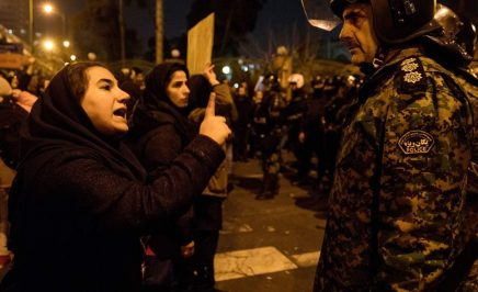 Street protest at night. A woman stands off against a security officer in riot gear. She points an index finger at him and shouts.