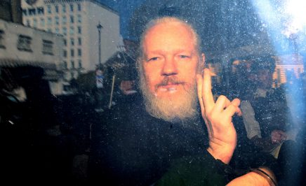Julian Assange, a man with a white beard, raises his hand in a peace gesture with media and police around him. Twilight evening, bright flash of light to the right.