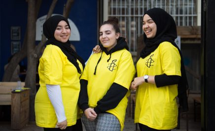 3 girls wearing bright yellow t-shirts, 2 with the hijab, smile in front of a tree and a dark blue wall. They are taking part in Amnesty France's Write for Rights event in Marseille.