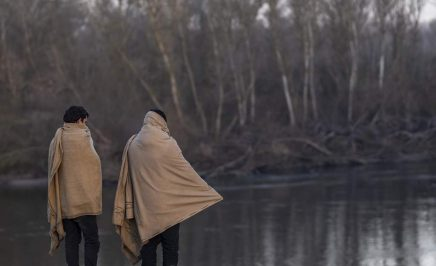Two refugees wrapped in blankets overlook a lake.