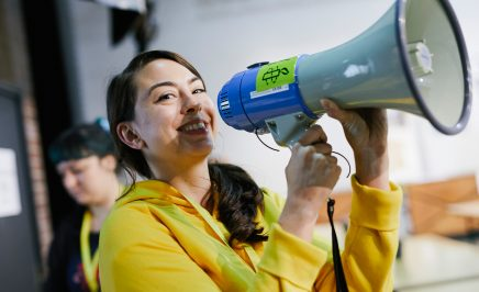 A young woman wearing a yellow hoodie and holding a loudspeaker