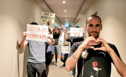 A small group of men stand in a hotel hallway, holding handmade signs asking 'Free us before COVID19 kills us'. One man creates heart symbol with his hands.