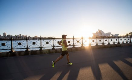 A man jogs along the harbour in Sydney, the sun low on the horizon and the Sydney Opera House in the background.